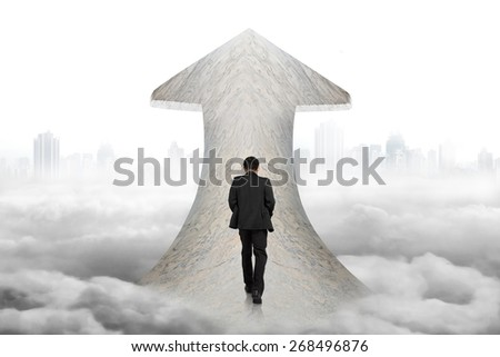 Black suit businessman walking on arrow up sign marble road with cloudy cityscape background - stock photo