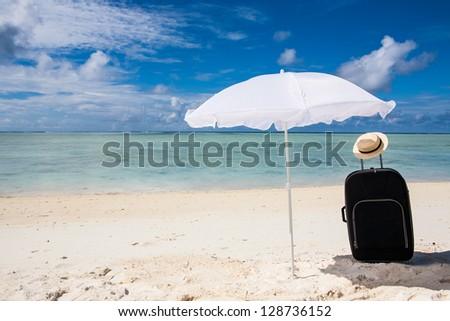 black suitcase sun hat and white sunhade at the beach - stock photo