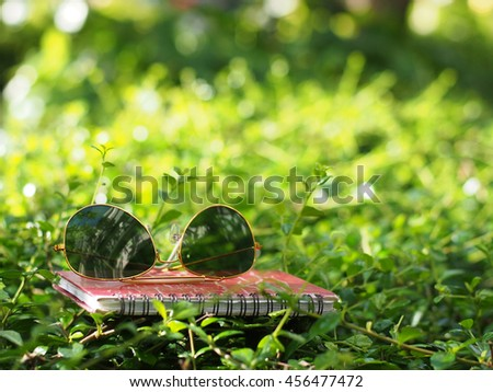 black sunglasses and notebook on green