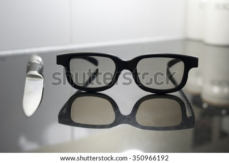 Black sunglasses next to knife on a black and white background
