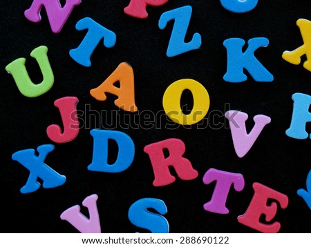 black surface covered with multiple colorful letters  - stock photo
