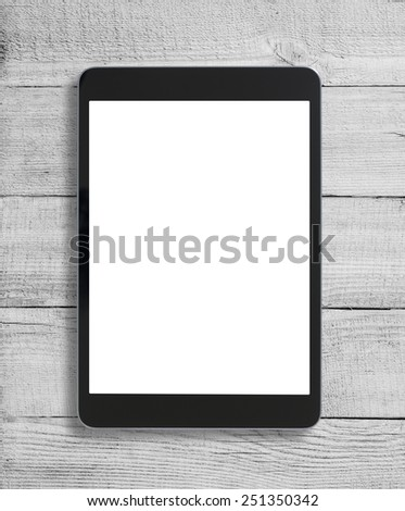 Black tablet pc similar to ipad on wood table background - stock photo