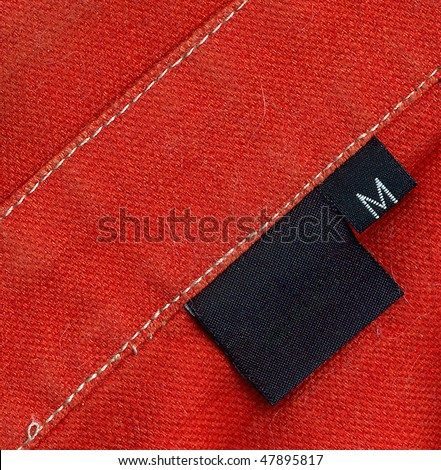 Black tag on a red denim textile - stock photo