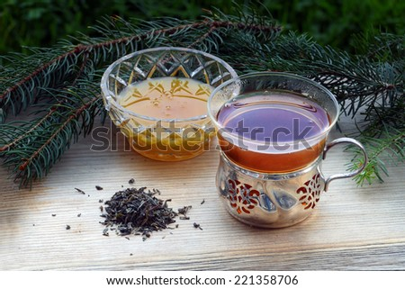 black tea and honey in nostalgic glasses and some loose tea on an old wooden board, fir tree in the background, suitable for autumn, winter and christmas, horizontal - stock photo