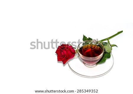 Black tea and red rose on white background