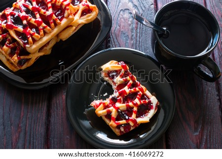 black tea cup, black plate with cookies and biscuits in a saucer bitten - stock photo