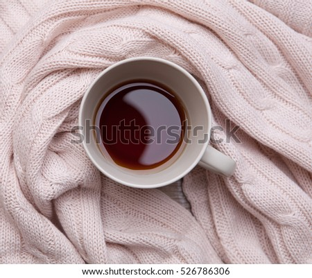 Black tea  in a ceramic cup wrapped around a warm knitted blanket