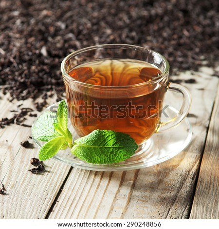 Black tea in a glass cup and saucer on a wooden table. Next to a cup of black tea scattered dry tea