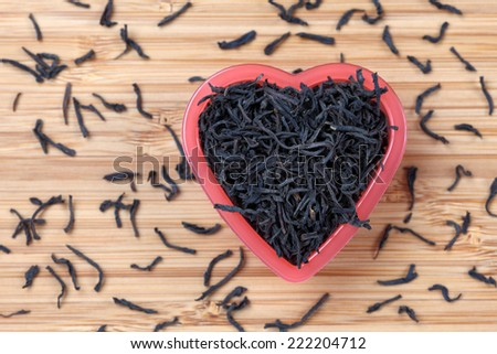 Black tea leaves in a heart bowl. Close-up. - stock photo