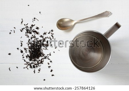Black tea on a table with a steel cup - stock photo
