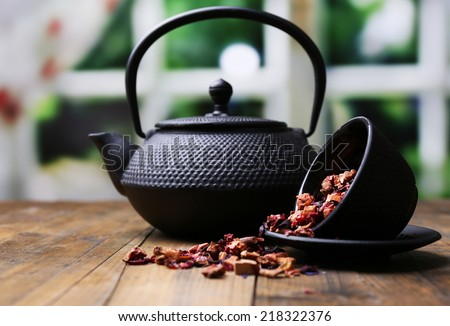 Black teapot, bowl and hibiscus tea on color wooden table, on bright background  - stock photo