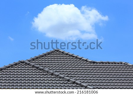 black tile roof on a new house with blue sky - stock photo