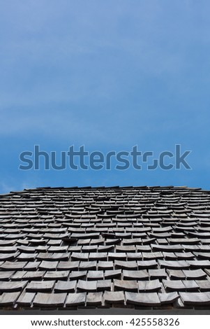 black tile roof on a old house with blue sky