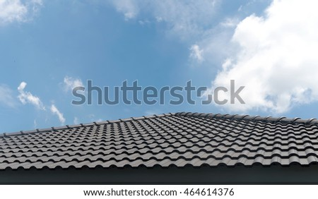 black tile roof with blue sky and cloud background