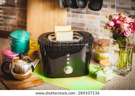 Black toaster with bread slices on kitchen table - stock photo