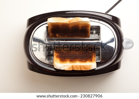 Black toaster with two slices of dark brown burnt bread. Studio shot, isolated on white background. - stock photo