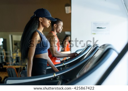 Black trainer and sexy african american woman on the treadmill in gym. Fitness concept - stock photo