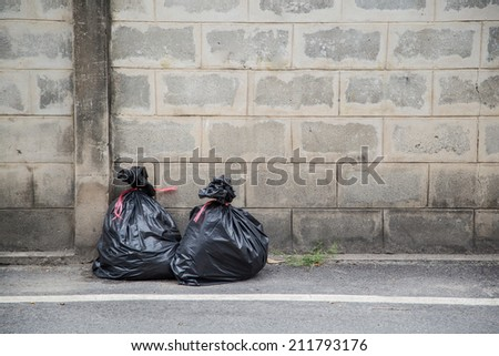 Black trash bags piled up against grungy urban wall - stock photo