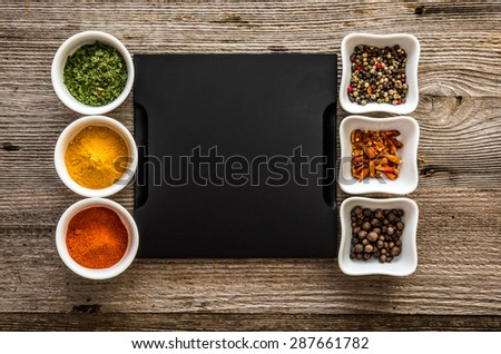black tray with different spices in bowls on both sides - stock photo