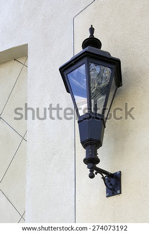 Black trimmed glass classic outdoor night light lamp on the wall - stock photo