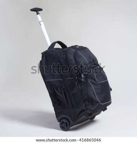 Black trolley bag on gray background - stock photo