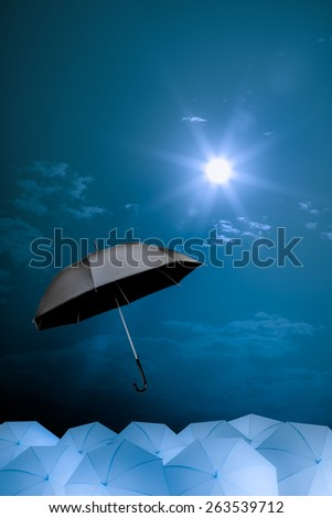 black umbrella fly out the mass of blue umbrellas, vision concept - stock photo