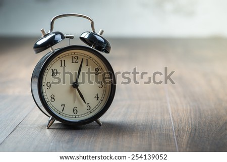 Black vintage alarm clock on a wooden floor - stock photo