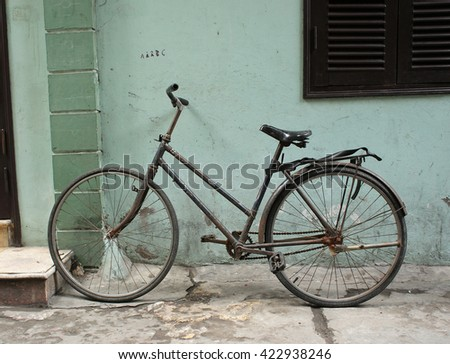 Black vintage bicycle leaning against a grunge wall (focus on bicycle)