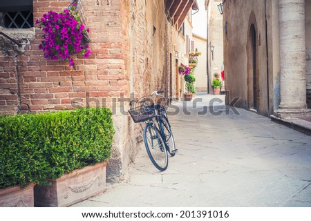 Black vintage bicycle left on a street in Pienza in Tuscany, Italy - stock photo