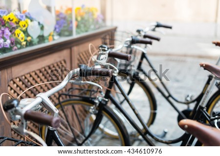 Black vintage bicycles in a bike stand in the city - stock photo