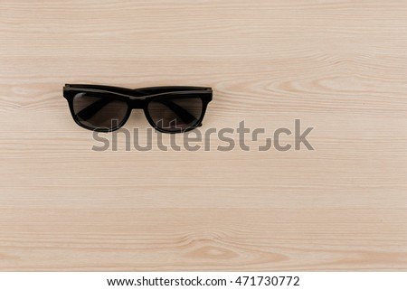 Black vintage sun glasses on wood, top view