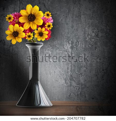 Black vintage vase with a bunch of flowers on grunge background. High resolution - stock photo