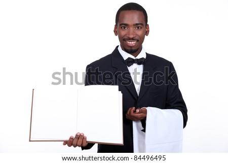 black waiter showing menu - stock photo