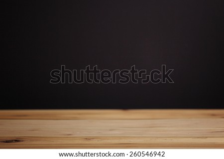 black wall and wood table background - stock photo