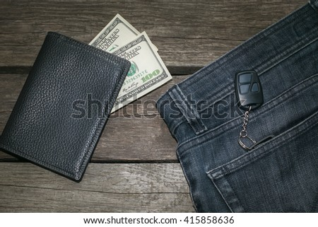 Black wallet, american dollar and key from car in jeans on wooden board. - stock photo