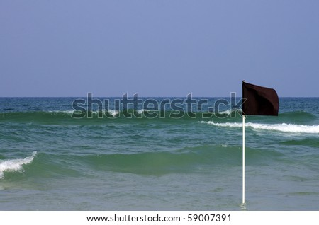 black warning flag in shallow water - stock photo