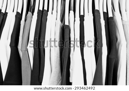 Black white and grey casual tops on a clothing rack, in black and white tones - stock photo