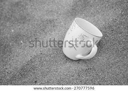 black & white concept for relaxation, coffee mug in sand - stock photo
