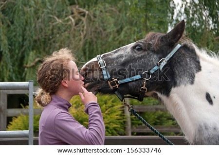 Black & white horse giving his owner kisses - stock photo