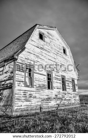Black & white old abandoned rustic barn with the morning sunlight on it