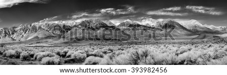 Black & White Panorama of the southern tip of the Sierra Nevada Mountains located in Central California under a clear blue sky with wispy white clouds. - stock photo