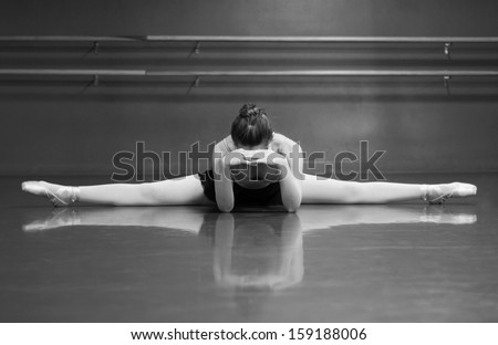 Black & White photo of a ballerina stretching her middle splits, in the studio with barre background. - stock photo