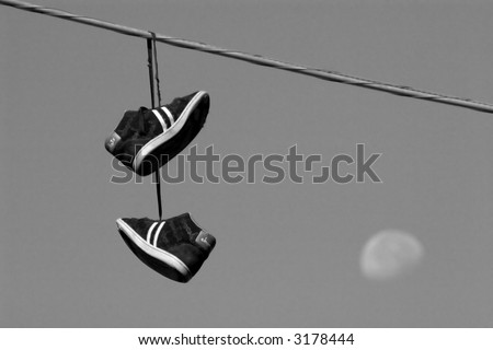 black & white photograph of sneakers hanging from a wire with Moon in background
