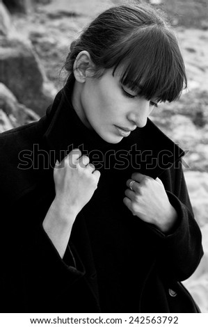 Black white portrait of elegant beautiful brunette woman model wearing a turtleneck sweater, holding her coat collar with hands, posing, looking down, near rocks on a bright sunny day. Autumn fashion. - stock photo