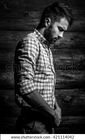 Black-white portrait of young beautiful fashionable man against wooden wall.  - stock photo