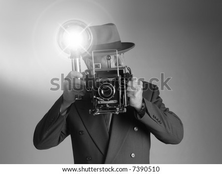 Black & White shot of a retro 1940's stylephotographer wearing a Fedora hat and holding a vintage camera with flash bulb flashing - stock photo