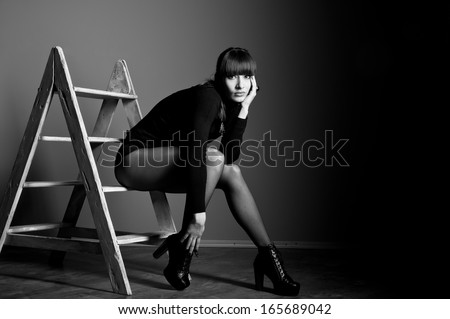 Black white studio portrait of confident beautiful slim woman model with awesome long legs wearing black body suit, boots with high heels, sitting on steps of staircase, looking at camera. Copy space - stock photo