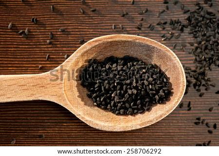 Black whole Nigella Sativa dry seeds portion on wooden spoon macro, Black cumin raw spice heap in day light, horizontal orientation, nobody. Polish name czarnuszka siewna. - stock photo
