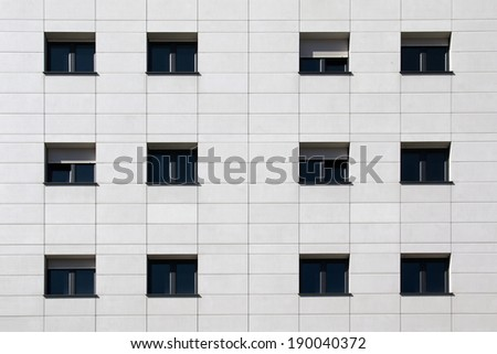 Black windows on white flagstone building facade - stock photo