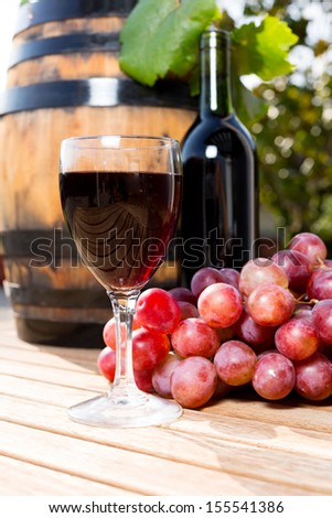 Black wine glass with freshly harvested grapes - stock photo